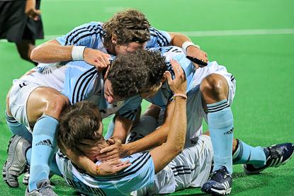 FESTEJO DE GOL. Manuel Brunet, Tomás Argento y Lucas Rey abrazan al goleador Facundo Callioni (Foto: FIH/Stanislas Brochier)